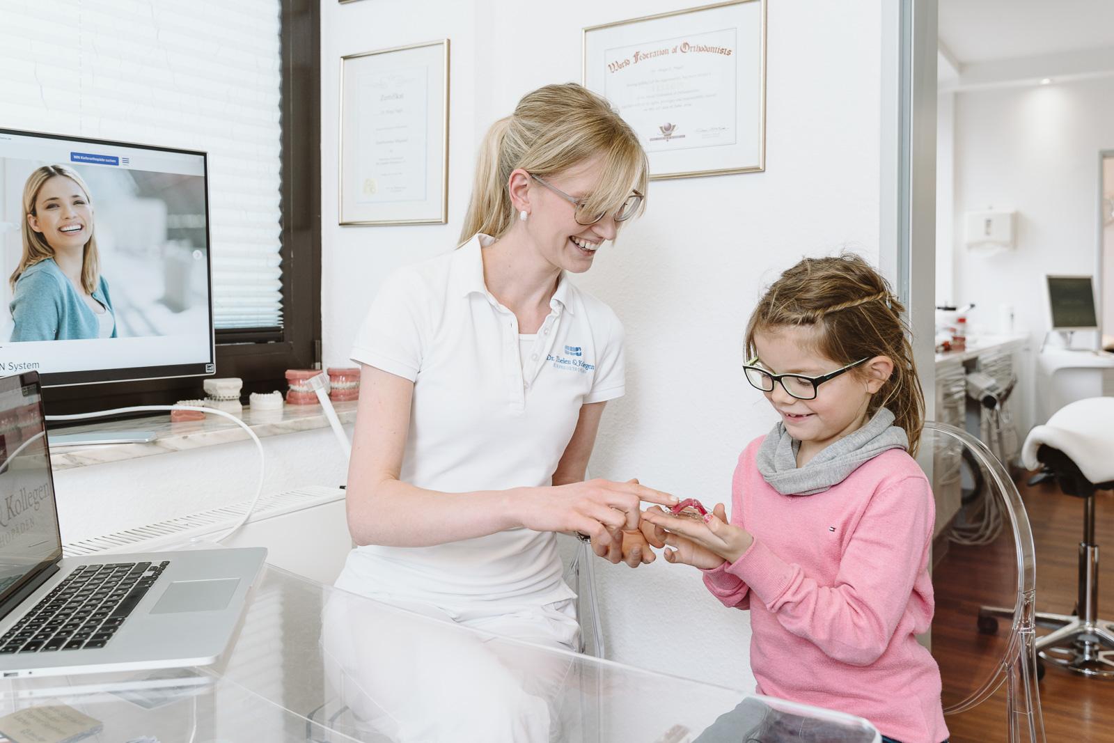 Unternehmensfotografie -  Kieferorthopädie Dr. Thelen - Patientin schaut sich eine Spange an