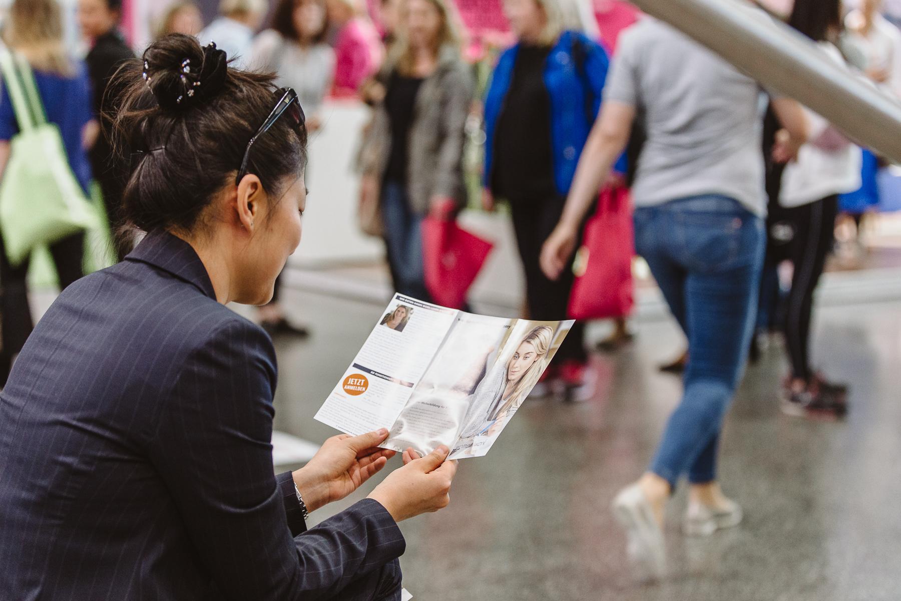 women&work- Kongressfotografie- Frau liest in Broschüre