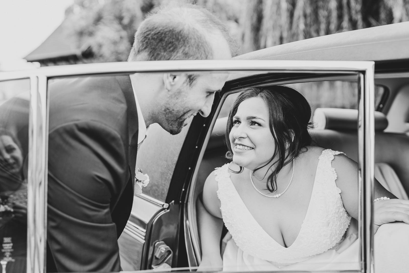 Hochzeitsfotografie - Mann hilft Braut aus dem Auto - sie himmelt ihn an
