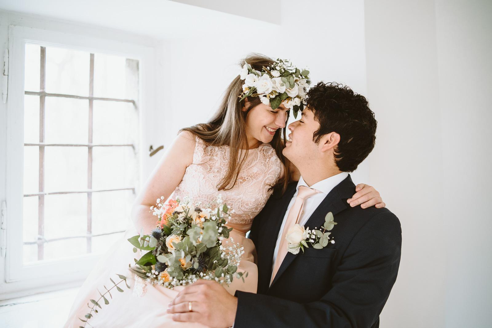 Hochzeitsfotografie - frisch getraut voller Freude zwischen Mann und Frau