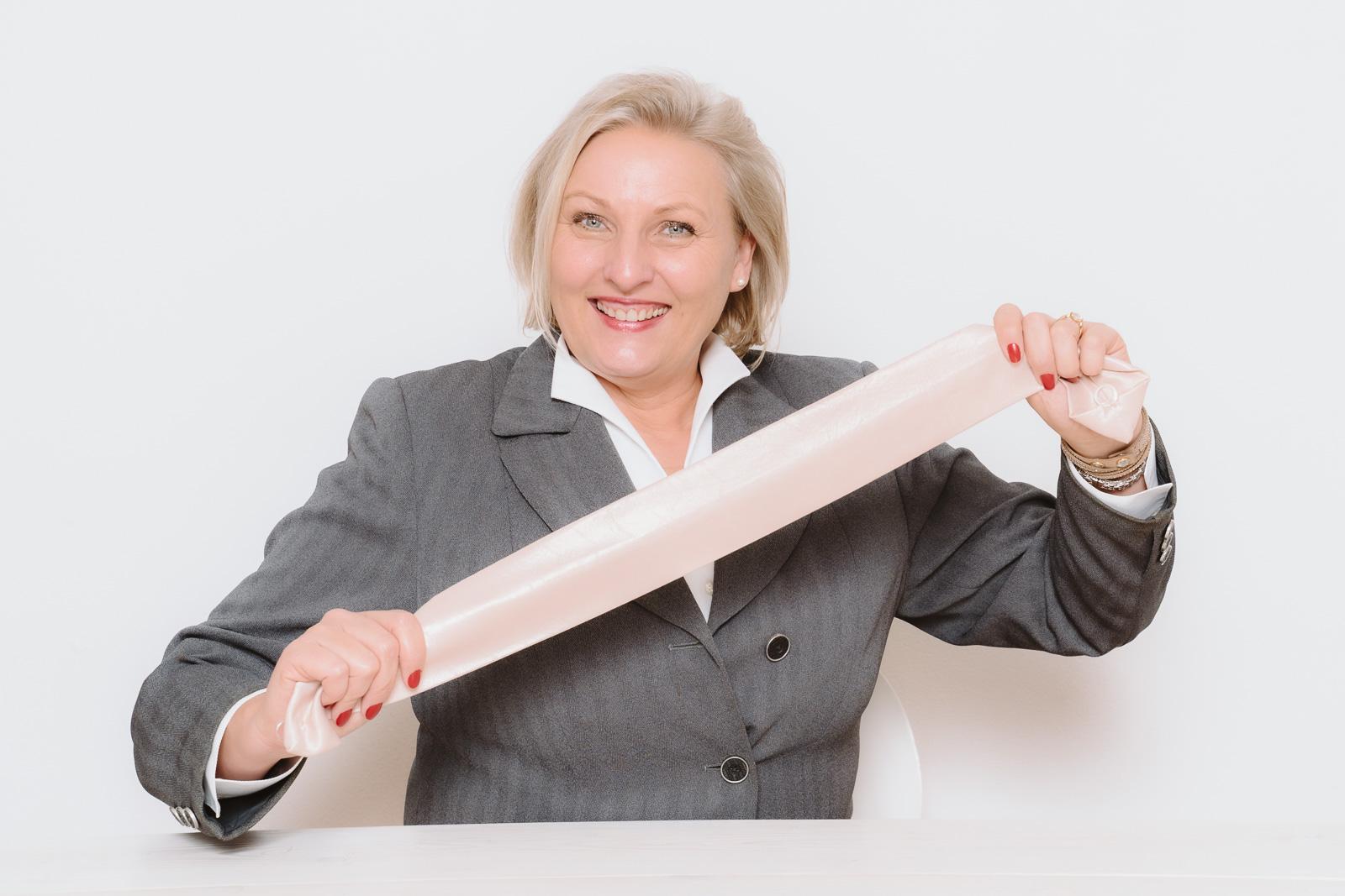 Businessporträts - Logopädin Kerstin Winterboer zeigt- der Knoten ist aus der Zunge - strahlendes Lächeln