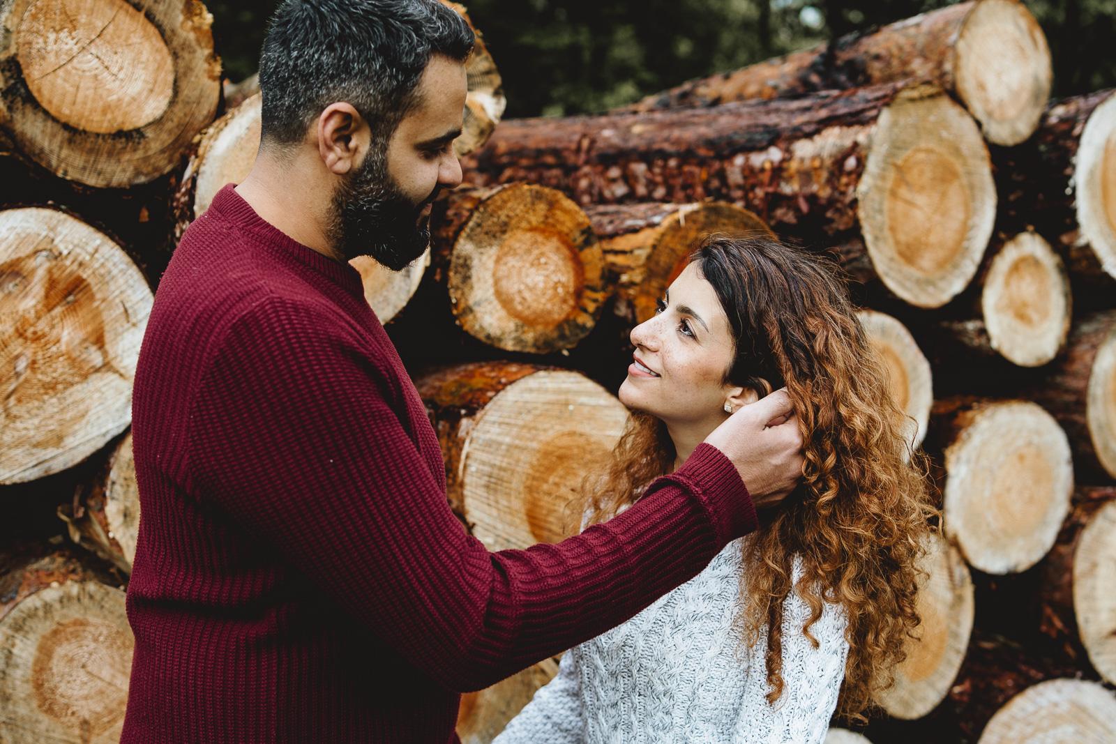 Paarfotografie-Mann und Frau vor Baumstämmen